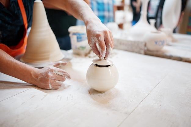 若い陶工の手は、白い粘土の鍋を巧みに作る陶芸家の手で生産されました。