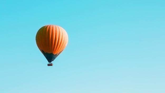 オレンジ色の風船が青い空を背景に舞い上がる