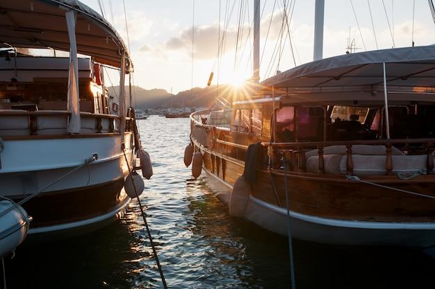 木漏れ日と美しい夕焼け空を背景に桟橋にヨット