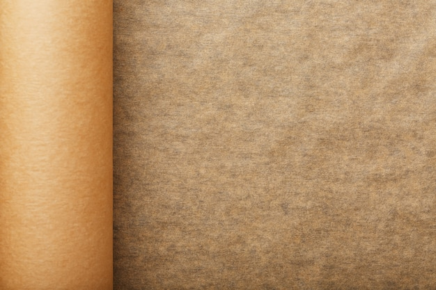 Рулон развернутой коричневой пергаментной бумаги для выпечки еды в темноте
