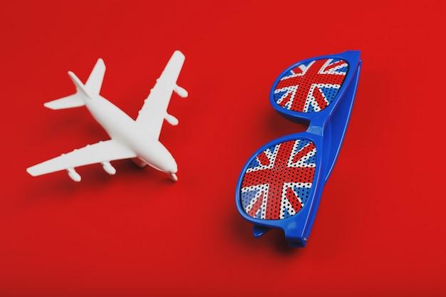 白い飛行機とイギリスの国旗とサングラス。イギリスへの旅行。