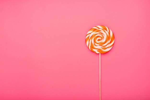 Оранжевый леденец на розовой поверхности
