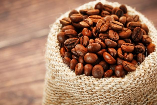 Свежеобжаренный ароматный кофе в мешковине на деревянной поверхности