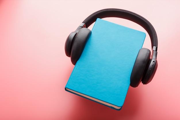 ヘッドフォンは、ピンクの背景、上面の青いハードカバーの本に着用されています。