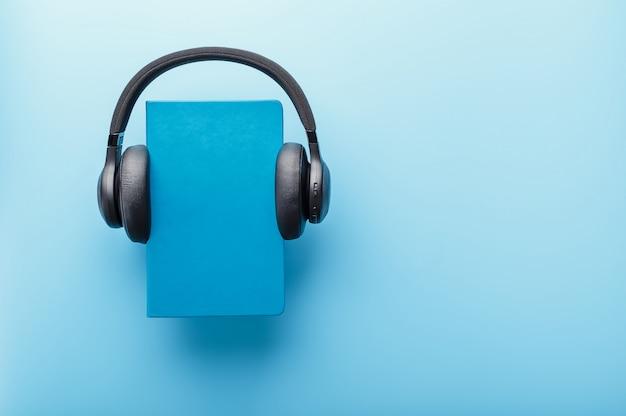 ヘッドフォンは、青い背景、上面に青いハードカバーの本に着用されています。