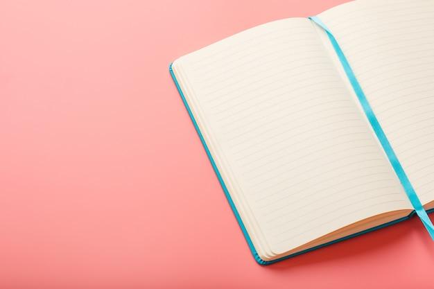 ピンクの背景に空白のページがあるラップトップを開きます。トップビュー、コピースペース