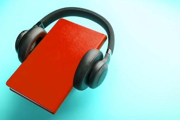 ヘッドフォンは、青の背景、上面に赤いハードカバーの本に着用されています。