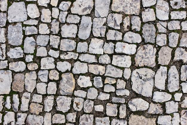 古い城の近くの灰色の石の石畳。