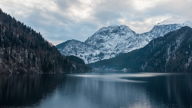 Зимнее озеро рица в абхазии с горами в снегу на заднем плане, поздним вечером.