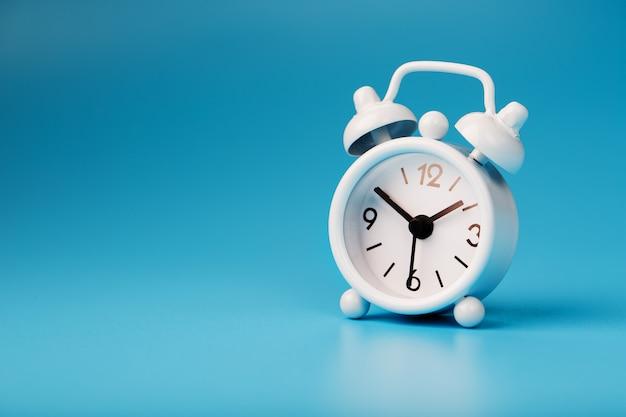 青の背景に白のレトロな目覚まし時計。テキスト用の空き容量のある時間の概念。