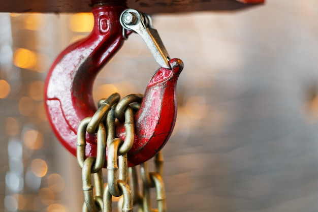 技術室の赤いフック付きの金属製チェーンハンドル。クレーン貨物フック。