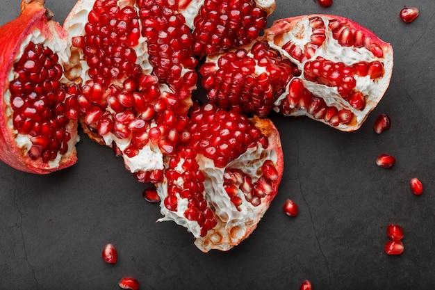Открытые плоды спелого открытого граната лежат.