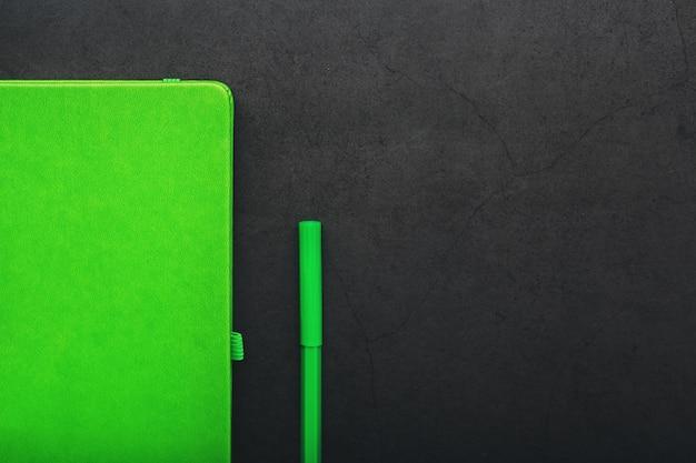 Зеленый блокнот с фломастером сверху.