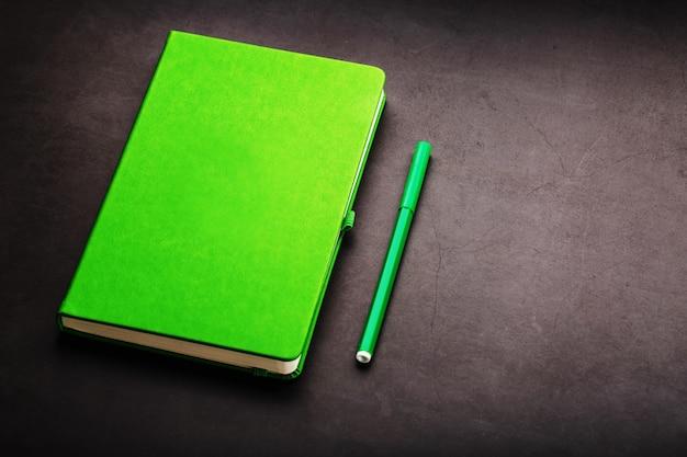 フェルトペンの上面を備えた緑のメモ帳。