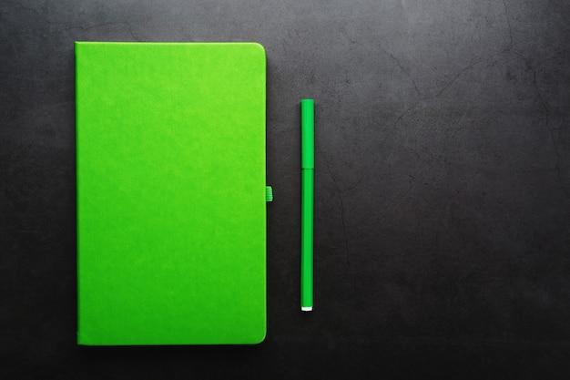 Зеленый блокнот с фломастером на черном фоне, вид сверху.