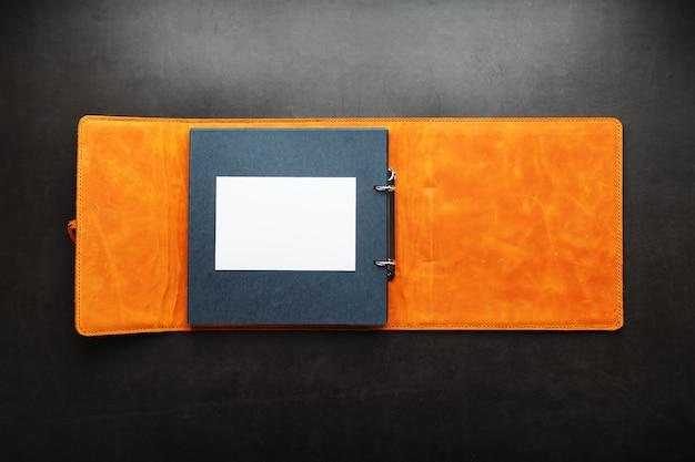 写真用の空きスペース、黒い紙の上の白いフレームを含むオープンフォトアルバム。アルバムカバーは茶色の手作りの本革で作られています