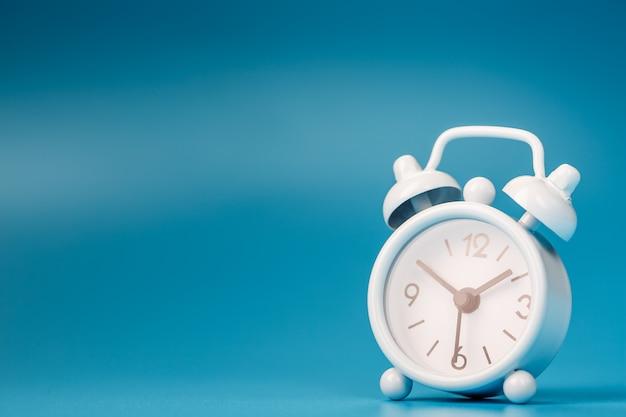 Белый ретро будильник на синем фоне. понятие времени со свободным пространством для текста.