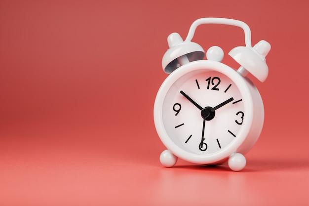 ピンクの背景に白のレトロな目覚まし時計。テキスト用の空き容量のある時間の概念。
