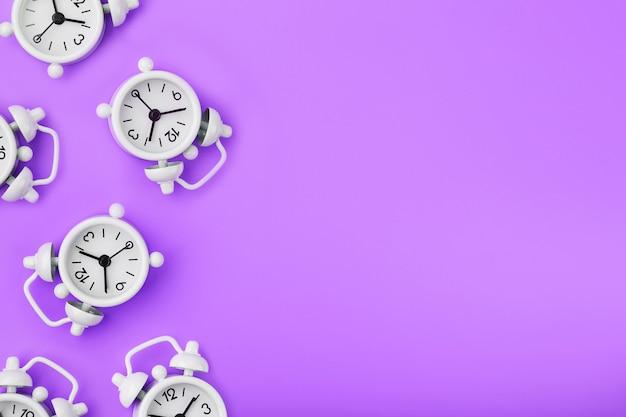 紫色の背景にパターンの形で多くの白い古典的な目覚まし時計のパターン。スペースのコピーを含む平面図、フラットレイ。
