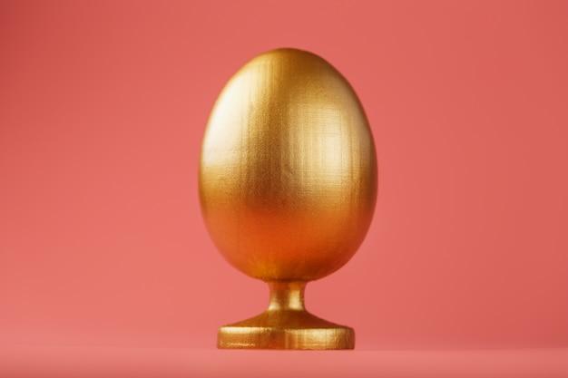 ミニマルなコンセプトを持つ黄金の卵。テキスト用のスペース。イースターエッグのデザインテンプレート。最小限のコンセプトのスタイリッシュなインテリア。