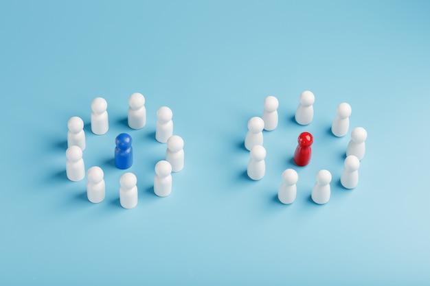 Две разные группы белых людей стоят вокруг синих и красных кандидатов в лидеры отдельно. конкуренция в бизнесе между фирмами и командами.