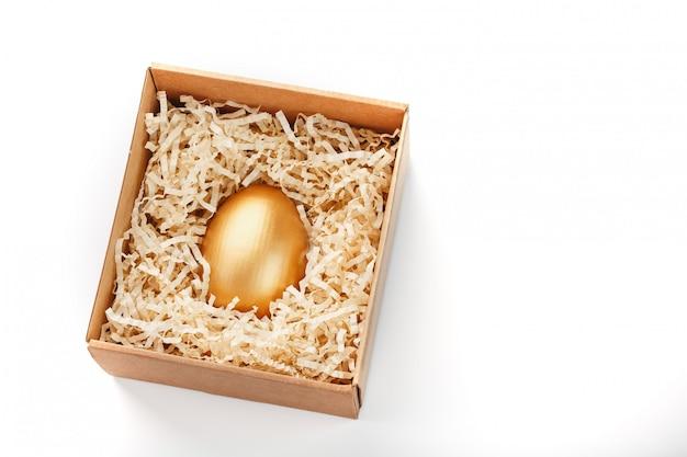 木箱に金で作られた卵。排他性とスーパープライズの概念。最小限の構成。
