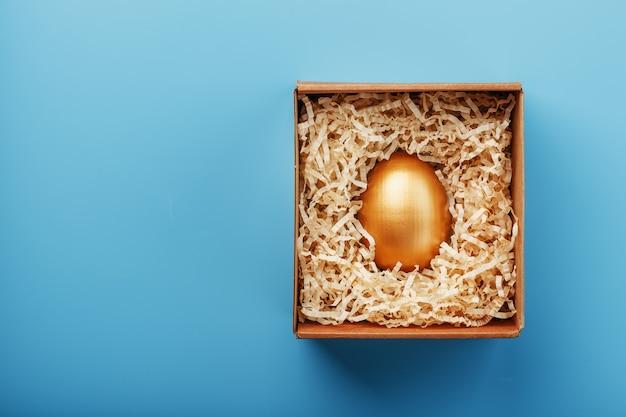 Золотое яйцо в коробке со стружкой концепция индивидуальности, эксклюзивности, лучший выбор, приз, особый сюрприз, редкий подарок.