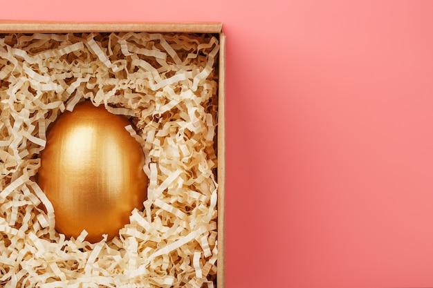 Золотое яйцо в коробке на розовом фоне. концепция эксклюзивности, лучший выбор, приз, особый сюрприз, дорогой подарок.