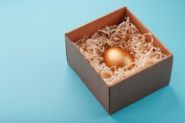 Яйцо из золота в деревянной коробке. понятие эксклюзивности и суперприза. минималистичная композиция.