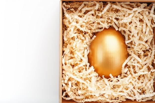 白地に木製の箱に金で作られた卵。独占権と超賞の概念。ミニマルな構成。