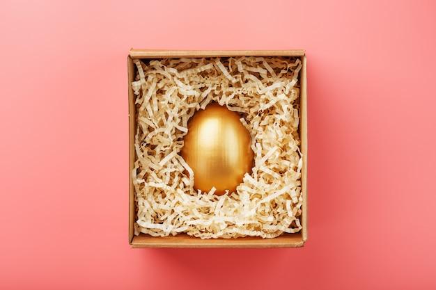 Яйцо из золота в деревянной коробке на розовом фоне. понятие эксклюзивности и суперприза. минималистичная композиция.