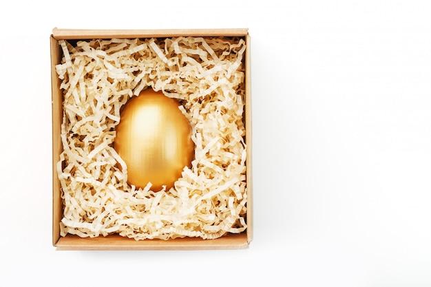 Яйцо из золота в деревянной коробке на белом фоне. понятие эксклюзивности и суперприза. минималистичная композиция.