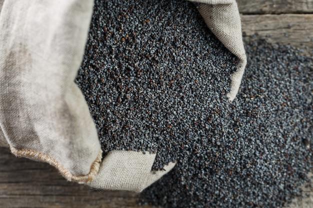 黄麻布の袋にケシの実。たんぱく質と油分が豊富でおいしい有用な種子。