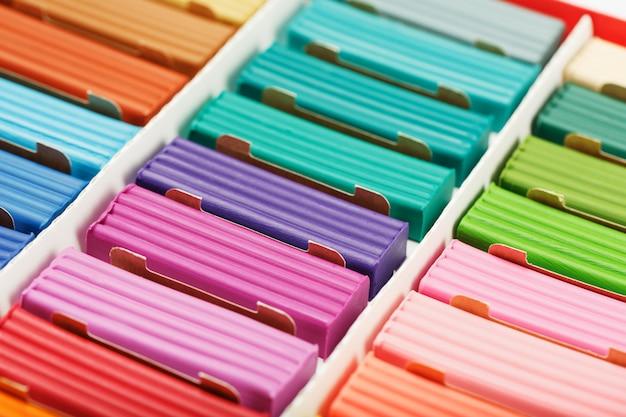 Пластилин в коробке из разноцветных кусочков на весь экран, материал для лепки.