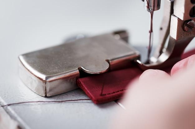 マスターの手とミシンで縫う皮革製品の針。手作業、ビジネス。