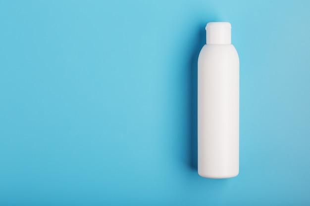 青色の背景に白のボトル。テキスト用の空き容量。