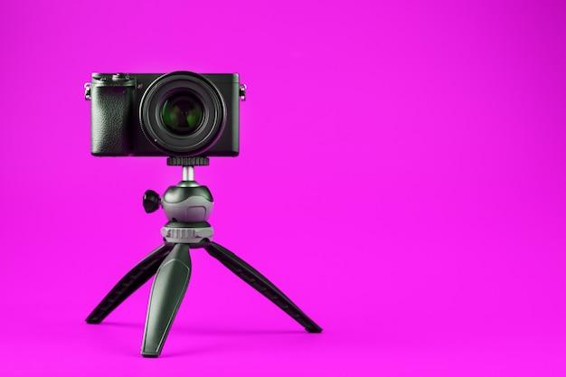 ピンクの背景に、三脚にプロ用カメラ。ブログまたはレポート用にビデオと写真を記録します。