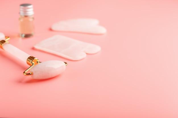 顔と体のケアのためのピンクの背景に天然ピンクのクォーツローラー、ヒスイの石、オイルで作られたグアシャマッサージツール。漢方薬の一部