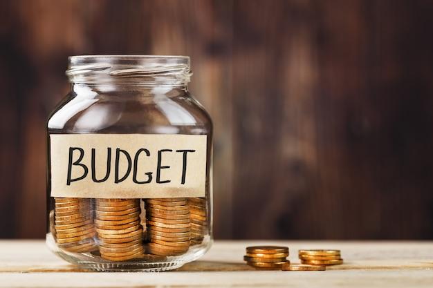 Стеклянная банка с деньгами и наклейка со словами бюджета на деревянный стол.