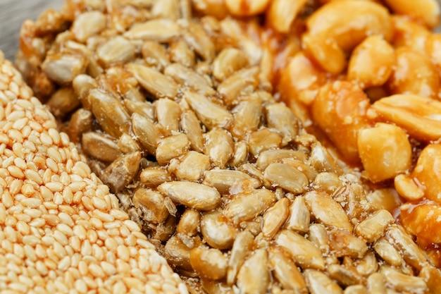 Ассорти из козинаков, конфет из семян подсолнечника, кунжута и арахиса, наполненных блестящей глазурью. макрос