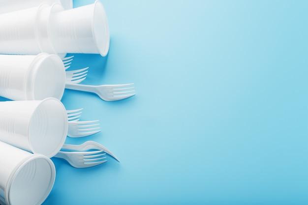 水色の壁にプラスチック製の食器。空きスペースのある使い捨てフォークとグラス。