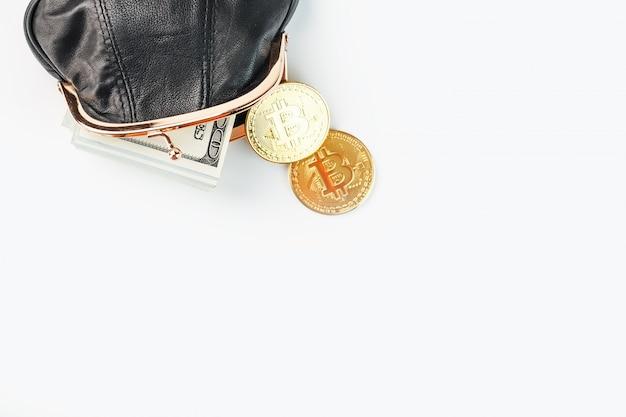 Открытый черный кошелек с деньгами, долларами и биткойн монеты на белой стене.