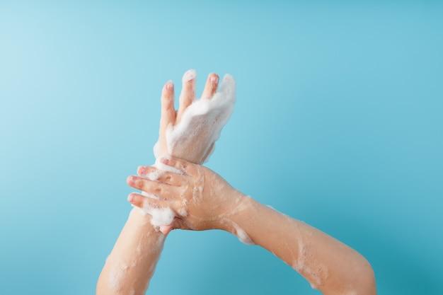 石鹸の泡で子供の手、青い壁、トップビュー。