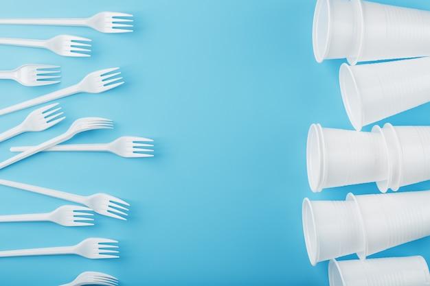 Блюда из белого пластика на синей стене.
