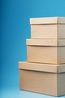 Почтовые картонные коробки на синем фоне крупным планом.