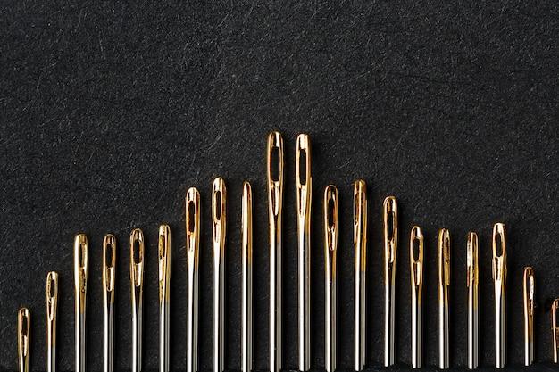 Набор золотых игл на черном фоне в ряд.