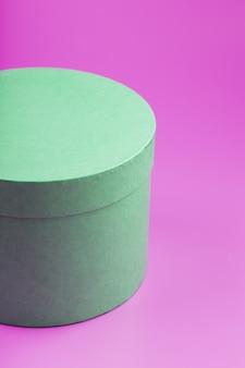 Круглая коробка на розовом фоне для подарка.