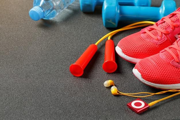 スポーツ用品、ダンベル、縄跳び、ボトル入り飲料水、スニーカー、プレーヤーのトップビュー