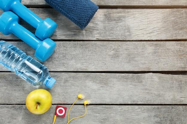 Спортивный инвентарь на сером, деревянном фоне, гантели, яблочная вода в бутылке, плеер
