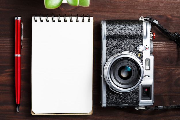 空白のメモ帳ページと暗い茶色の木製のテーブル、電話と緑の花を持つヴィンテージのテーブルに赤ペンで古典的なカメラ